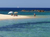 Vom Strand blickt man auf kleine, felsige Inseln.